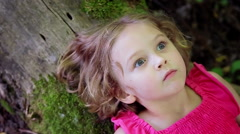 Closeup Of Curious Child Laying On A Log, Staring Wide Eyed Into The Trees Above - stock footage