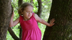 Child Pouts Dramatically In A Tree, Camera Pans Down To Her Feet - stock footage