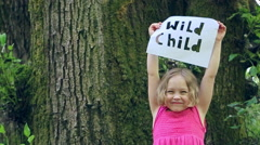 "Happy Little Girl Holds Up A Paper Sign ""Wild Child"" Cut Out, She Runs Away Stock Footage"