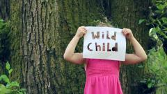 "Cute Little Girl Holds Up A Paper Sign With ""Wild Child"" Cut Out, She Lowers It Stock Footage"