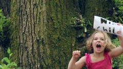 "Little Girl Holds A Paper Sign With ""Wild Child"" Cut Out, She Growls And Dances Stock Footage"