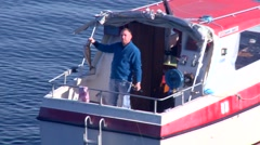 A man holds up a large trout from his boat on a lake in Norway. Stock Footage