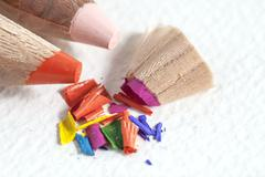 color pencils shavings on white paper - stock photo
