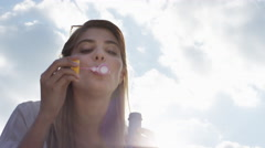 Beautiful woman blowing bubbles outdoors sunshine freedom blue sky is pretty Stock Footage
