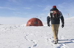 Hiker Approaching Emergency Shelter in Castle Rock Loop, Ross Island, Antarctica - stock photo