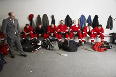 Coach and Hockey Players in Dressing Room Stock Photos