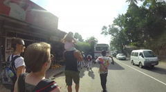 Man carrying little blond girl on his shoulders while walks down the street. Stock Footage