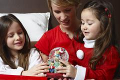 Mother and Daughters Looking at Christmas Snow Globe Stock Photos