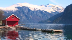 Beautiful wide shot of the fjords of Norway with red boathouse. - stock footage