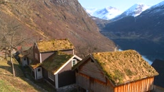 Thatch roofed traditional houses line the fjords of Norway. - stock footage