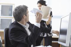 Businessman Throwing Paper Airplane at Businesswoman in Office Kuvituskuvat