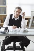 Businessman Sitting at Desk Writing - stock photo