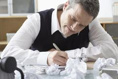 Businessman Sitting at Desk Writing Stock Photos