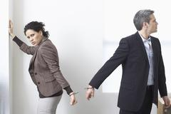 Businessman and Businesswoman Handcuffed Together Stock Photos