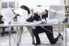 Business People Trying to Hold onto Paperwork Blowing Around on Desk Stock Photos