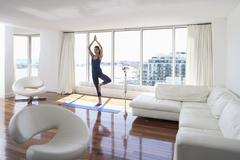 Woman Practicing Yoga in Condominium Stock Photos