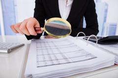 Midsection of young businesswoman scrutinizing bills with magnifying glass at Stock Photos