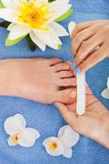 cropped image of woman undergoing pedicure process in beauty salon - stock photo