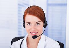 Closeup of smiling female customer service representative with microphone Stock Photos