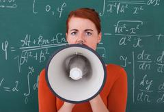 Side view of young female student screaming on megaphone against blackboard Stock Photos