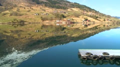 Villages and farms cast a perfect reflection in the fjords of Norway. - stock footage