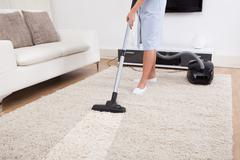 Cropped image of young maid cleaning carpet with vacuum cleaner at home Stock Photos