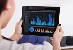 Cropped image of young woman using analytics application on digital tablet Stock Photos