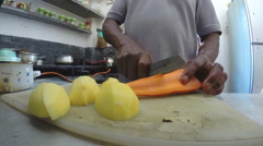 Slow motion of man slicing carrots and potatoes with a knife in kitchen. Stock Footage