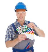 Portrait of confident mid adult male handyman showing color swatches over whi Stock Photos