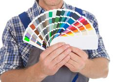 Midsection of handyman showing fanned color swatches over white background Stock Photos