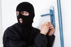 Alert thief looking away while opening door with tool during house breaking Stock Photos