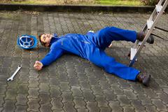 full length of young unconscious technician fell from ladder on street - stock photo