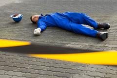 Full length of young unconscious technician lying on street Stock Photos