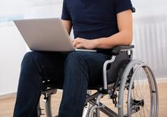 Cropped image of young handicapped man using laptop while sitting on wheelcha Stock Photos