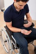young handicapped man holding medicine while sitting on wheelchair at home - stock photo