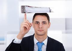 portrait of businessman balancing binder on head with index finger in office - stock photo