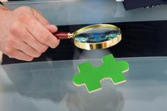 midsection of businessman scrutinizing green puzzle piece with magnifying gla - stock photo