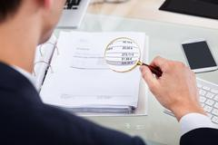 Cropped image of auditor examining invoice with magnifying glass at desk Stock Photos