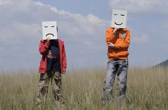 Boys in Field holding Drawn Facial Expressions Stock Photos