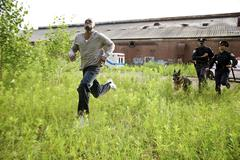 Police Officers and Police Dog Chasing Suspect Through Field - stock photo