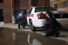 Police Officers Crouching Behind Police Car With Guns Drawn Stock Photos