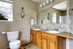 bathroom cabinet with two sinks and tile trim - stock photo