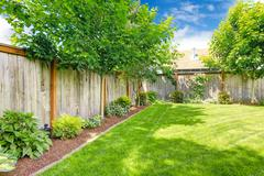 Fenced backyard with lawn and flower bed Stock Photos