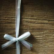 decorative white ribbon and bow over wooden background - stock photo