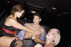 Women Undressing Man in Back of Limousine Stock Photos