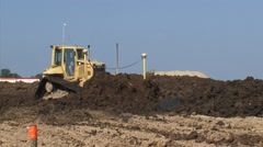 Tracked shovel shifts layer of clay for dike building - medium shot Stock Footage