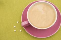 Sweetener Tablets by Cup of Coffee - stock photo