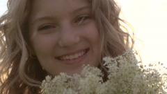 Beauty happy girl with curly blond hair smelling wild flowers Stock Footage