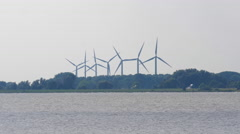 4K Wind power farm in motion with turbine towers rotating next to the coast Stock Footage