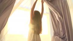 Beauty girl opens curtains on big window and let the light in the room - stock footage